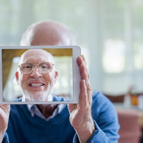 Senior man taking self portrait on digital tablet